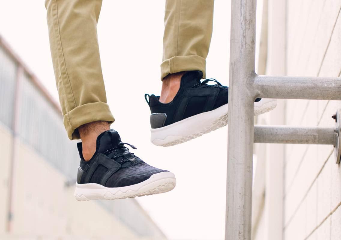 man wearing black teva trainers