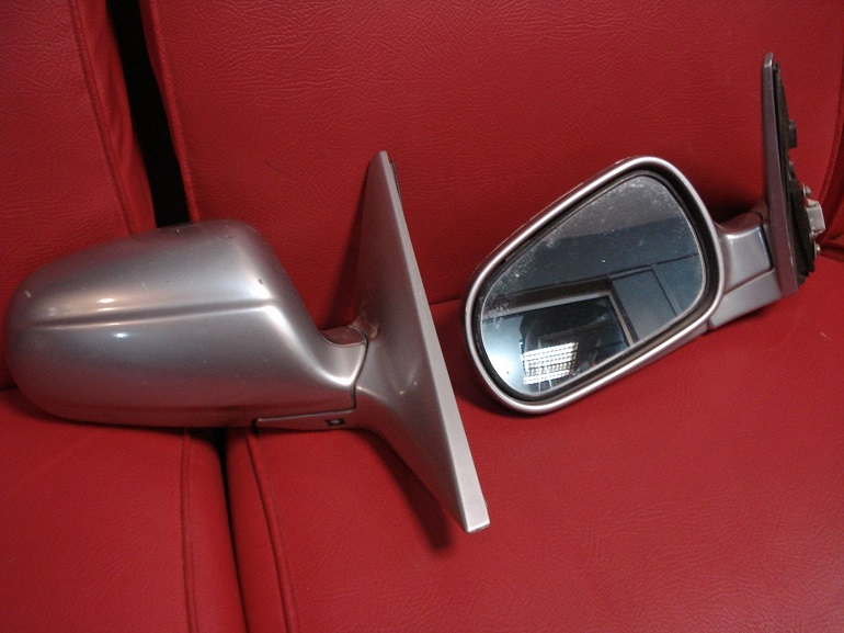 two toyota corolla's side mirrors on red seat