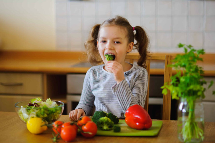 girl eating broccoli cold vitamins