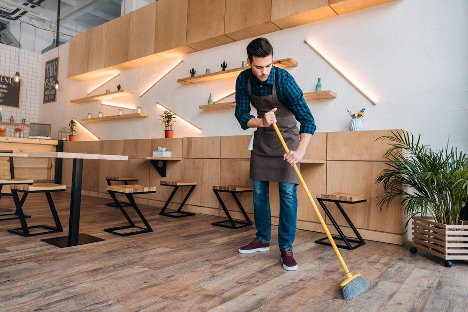 man cleaning cafe's vinyl flooring