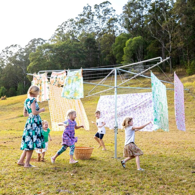 mother hanging clothes on a rotary clotheslines