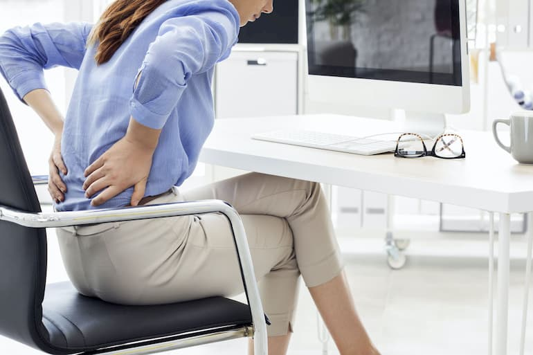 woman with back pain sitting on office chair