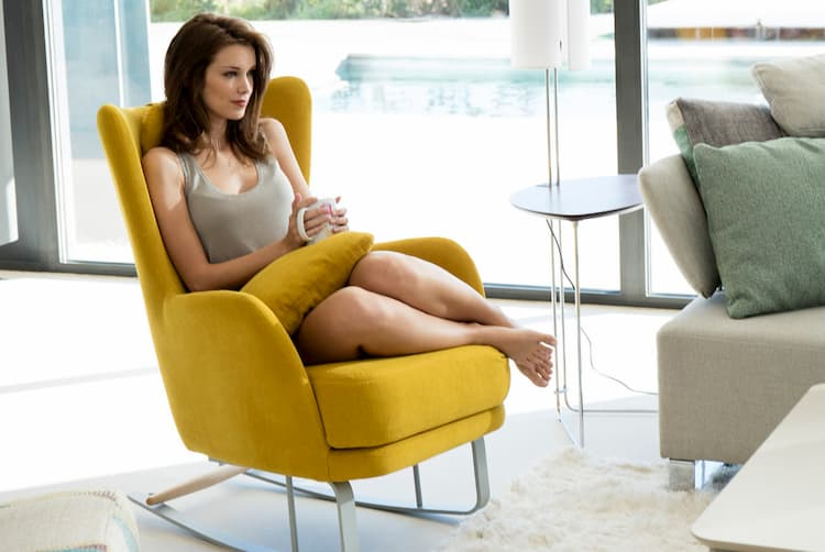 a woman sitting on a modern yellow rocking chair