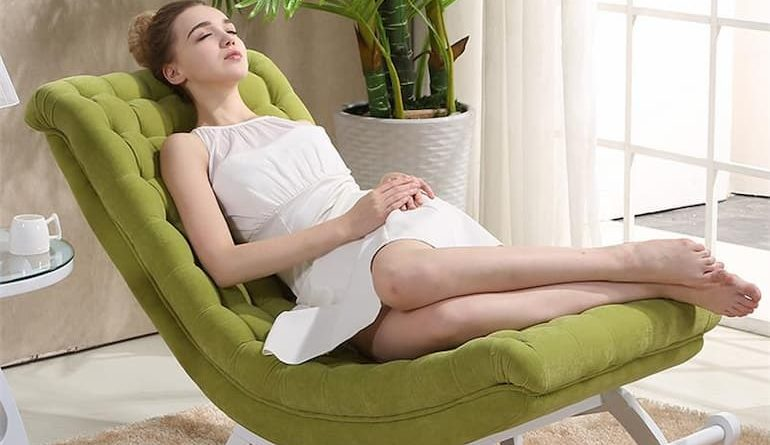 girl laying on a green chair in the living room