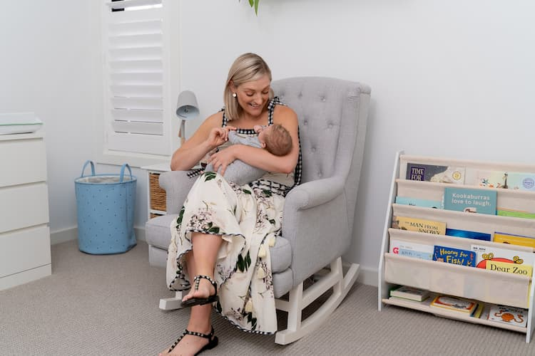 woman sitting on a rocking chair with her baby