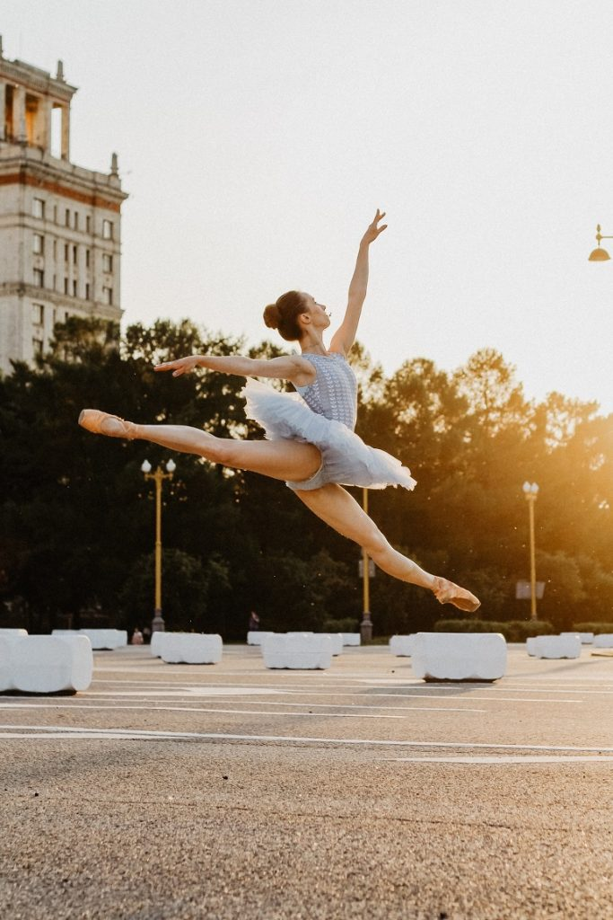 picture of ballerina on a parking lot in a tutu and ballet shoes