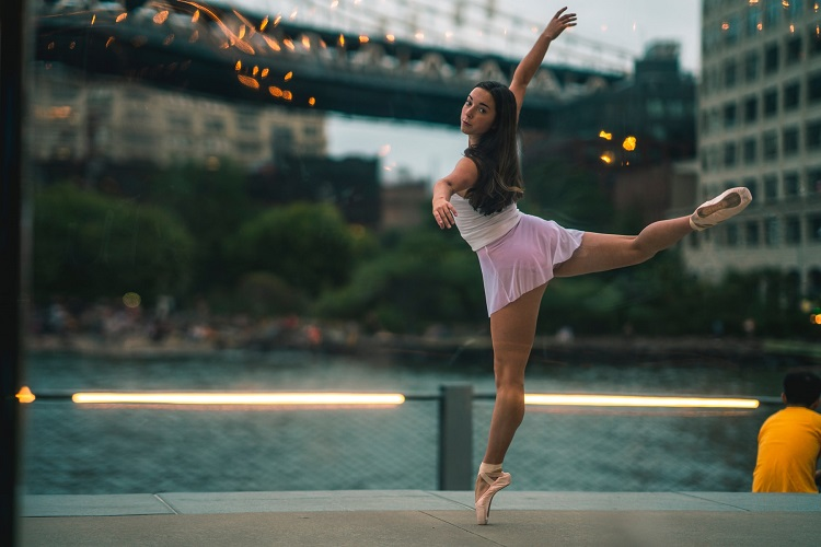 picture of a girl ballerina beside a river in a city park dancing with comfort and confidence