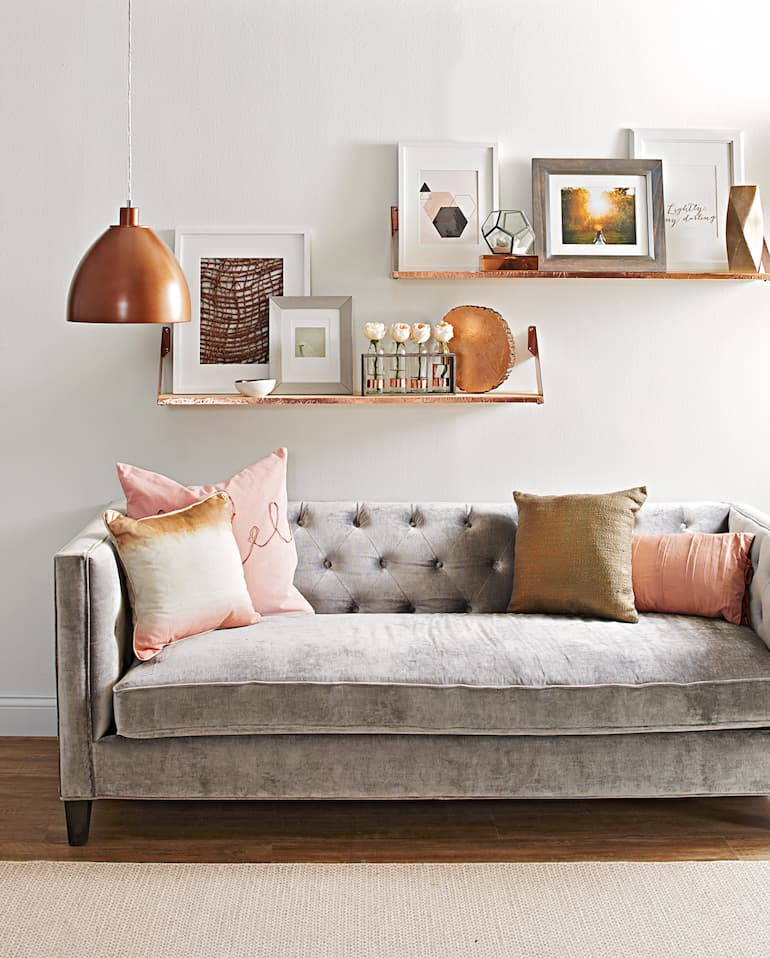 modern sofa bed with decorative pillows shelves and artwork