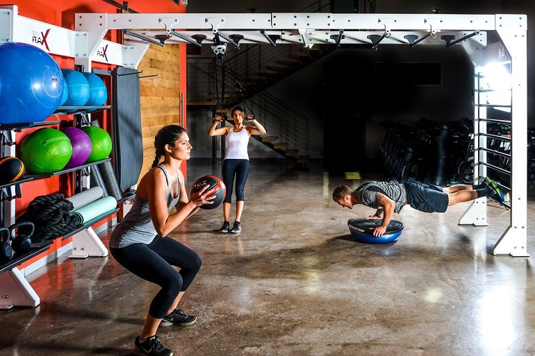 two women and men working out in gym